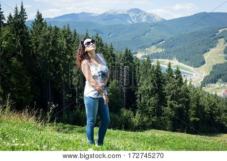 Beautiful girl is standing on a mountain in Carpathians. The mountains and woodland in the background. Bukovel. Ukrainian Carpathians.