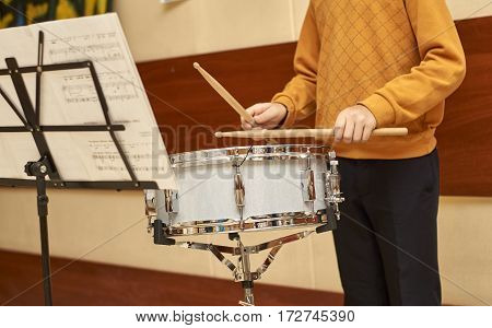 Boy playing drum looking to notes during the school fair