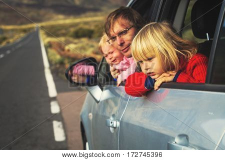 family travel by car- father with two little kids driving on road