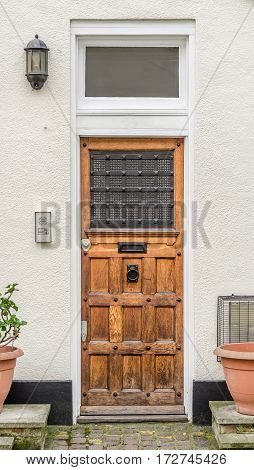 old style entrance to the building pots with green plants the entrance from the sidewalk to the building a large wooden door vintage