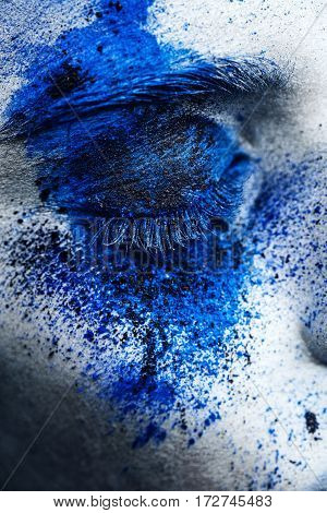 close up eye of fashion model girl with colorful powder make up. Beauty woman with bright blue makeup and white skin.  Abstract fantasy make-up, art design.