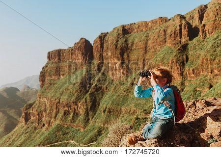 little boy looking through binocular on travel in mountains
