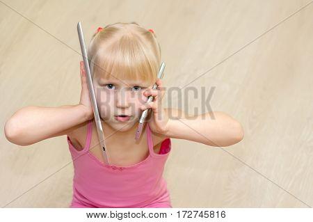 Little Girl In A Pink Dress Talking On Cell Phone And Tablet