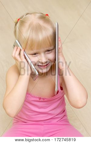 little girl in a pink dress smile and talking on cell phone and tablet at the same time
