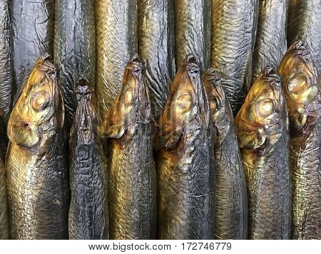 Food background - Dried and smoked fish stacked pile closeup