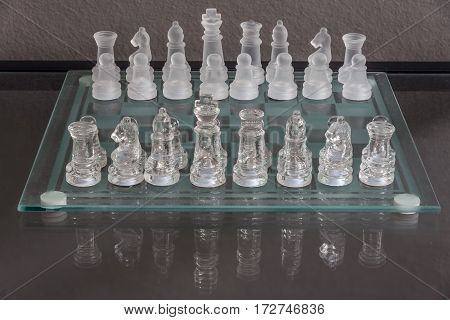 Setup of the start of chess game on a glass chessboard with reflection