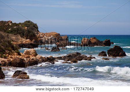 Waves crashing onto rocks at San Blas beach Gozo Malta
