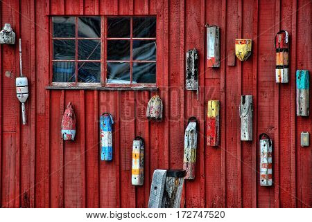 Red wood wall with several colored buoy