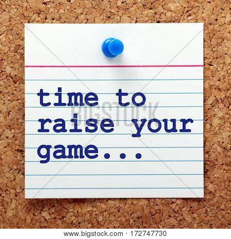 The words Time to Raise Your Game in blue text on a note card pinned to a cork notice board as a reminder