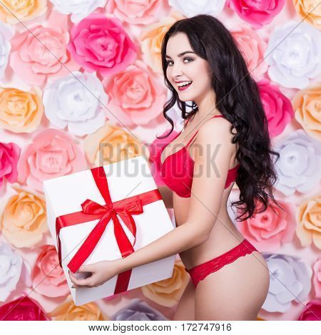 Sexy Young Woman In Red Lace Lingerie With Gift Box Over Paper Flowers Background