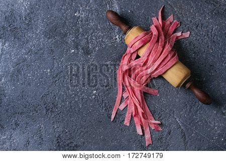 Fresh raw uncooked homemade pink beetroot pasta tagliatelle on wooden rolling pin over dark texture concrete background. Top view with space.