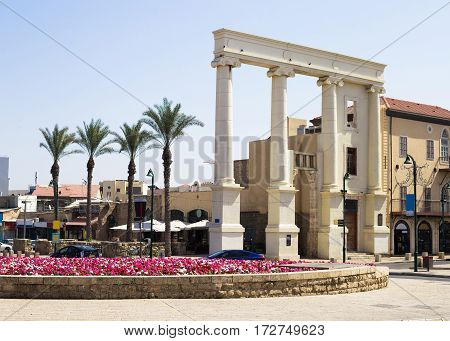 Colonnade in the Jaffo an old part of Tel Aviv Israel. Colorful flowers palm trees and cars. Sunny summer day