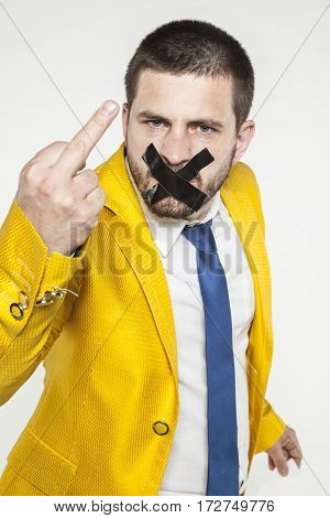 Businessman With Tape On His Mouth Showing The Middle Finger
