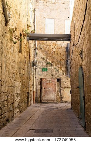 An alley in an ancient old city Acre Israel. Stone walls oriental architecture.