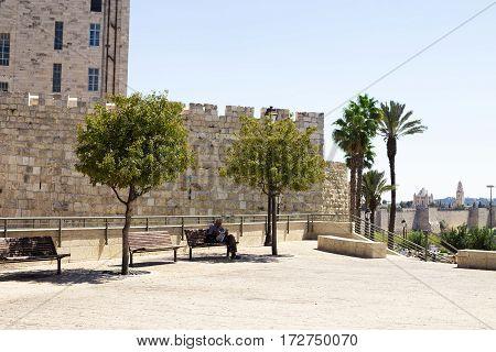 JERUSALEM ISRAEL - CIRCA SEP 2016: Old walls of Jerusalem near the Jaffa Gate. A man sitting on a bench and reading a newspaper