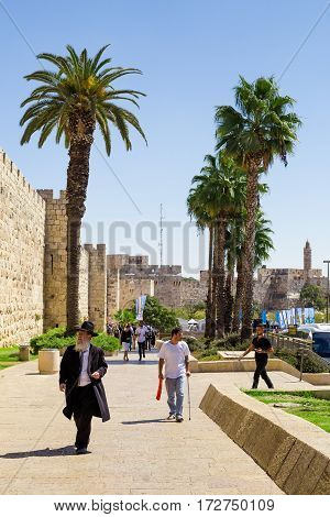 JERUSALEM ISRAEL - CIRCA SEP 2016: Alley leading to the Jaffa Gate. Tall palm trees tourists and a typical Jew in the foreground