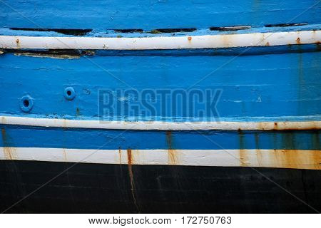 Close up side view of old abandoned blue painted boat
