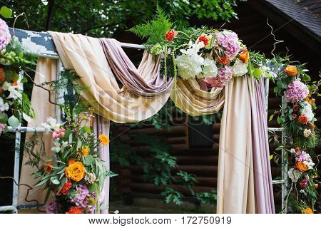Beautiful wedding ceremony outdoors. Wedding arch made of cloth and white and pink flowers on a green natural background. Old doors rustic style. Arch of flowers