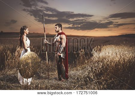 Side view of couple meeting after war in field at night, looking each other. Beautiful brunette woman wearing in dress like greece style holding iron shield and husband warrior wearing like spartan.