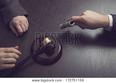 Detail of a criminal offering bribe money to a corrupted judge. Selective focus