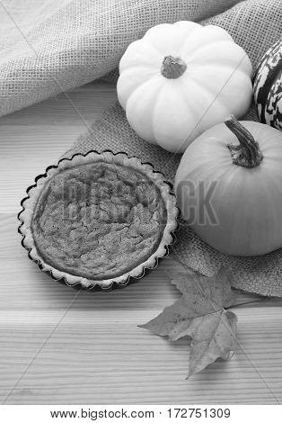 Mini pumpkin pie on a table with autumn gourds and maple leaf