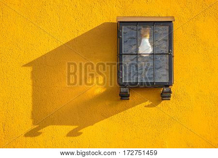 Hidden lamp on a yellow stone wall