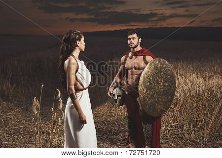 Side view of woman wearing like greece in white dress and  man warrior with shield wearing like spartan. Portrait of couple meeting after war in field, looking each other.