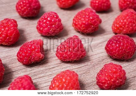 Red ripe raspberry lie on a wooden background. Copyspace flat lay top view. Macro of raspberry on table