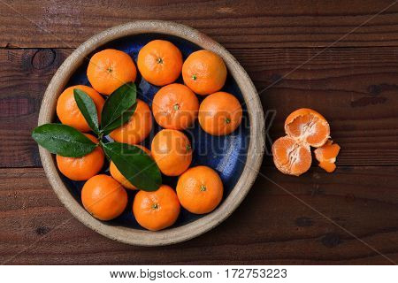 Top view of a plate of fresh ripe Mandarin Oranges in a rustic wood table with one peeled piece of fruit.