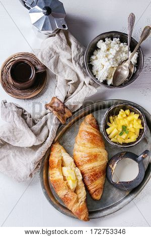 Breakfast with two croissant, butter, cup of coffee, cottage cheese and sliced mango fruit, served on serving metal tray with textile napkin on white and gray concrete texture background. Top view.
