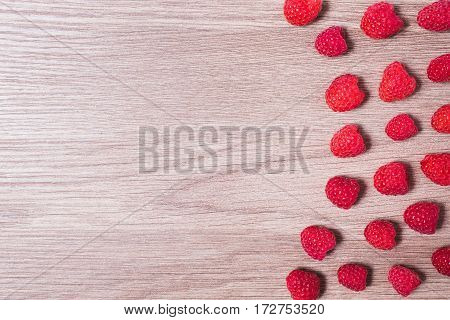 Red ripe raspberry lie on a wooden background. Copyspace flat lay top view. Raspberry on a table