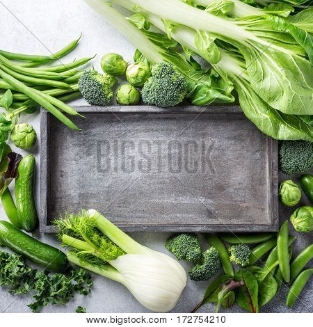 Background with assorted green vegetables and old wooden tray on light gray stone table top. Healthy food concept with copy space.