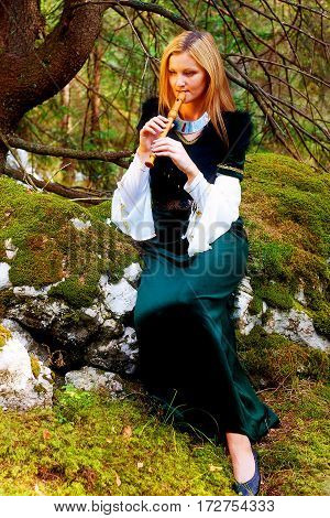 beautiful girl in a historical costume playing her flute in forest. and light graphic effect