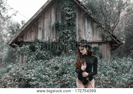 Picture of a beautiful witch with a bouquet of roses on Halloween