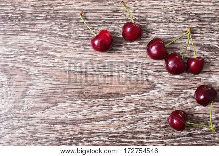 Red ripe juicy sweet cherry lies on vintage wooden background. Sweet summer berries. Flat lay top view. Copyspace healthy food of sweet cherry