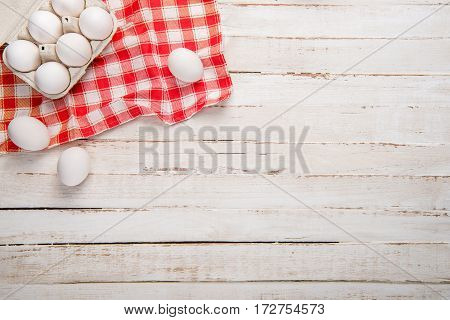 Top view of raw chicken eggs in egg box on checkered tablecloth on white wooden table