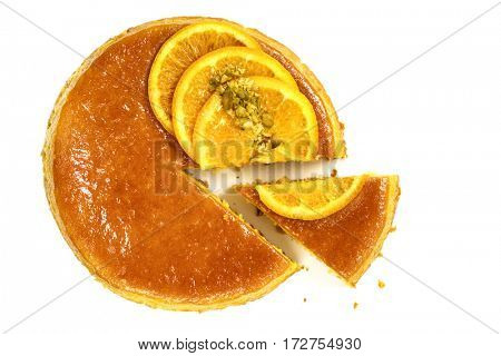 Flourless orange cake with wedge cut out.  Top view, isolated.