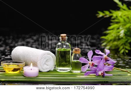 orchid with candle oil ,soap ,towel on green plant on wet background