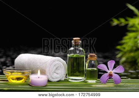 spa concept –orchid and ,stones , towel,candle on green long leaf