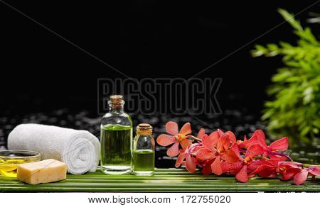 Red orchid with candle oil ,soap ,towel on green plant on wet background