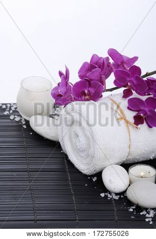 Spa setting with branch orchid, towel, cinnamon, candle