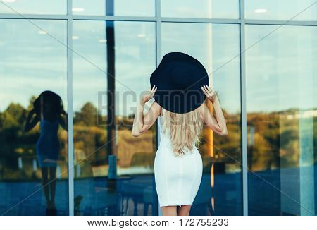 Luxury travel vacation woman standing back near hotel. Elegant young lady wearing sexy dress and big hat on holidays.