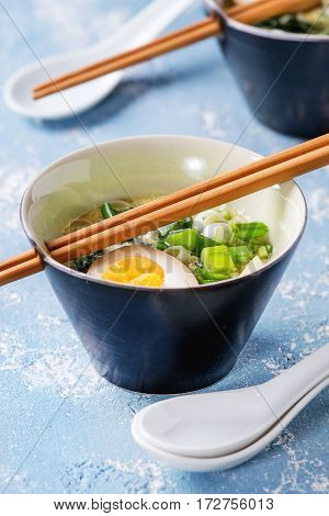Two bowls with asian style soup with scrambled eggs, half of marinated egg, spring onion, spinach served with wood chopsticks and spoons over blue texture concrete background.
