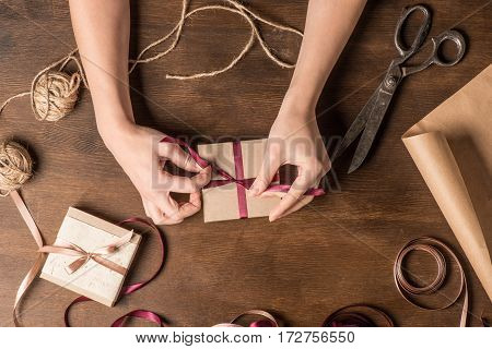 top view of hands tying ribbon on gift with old scissors and ropes on wooden table