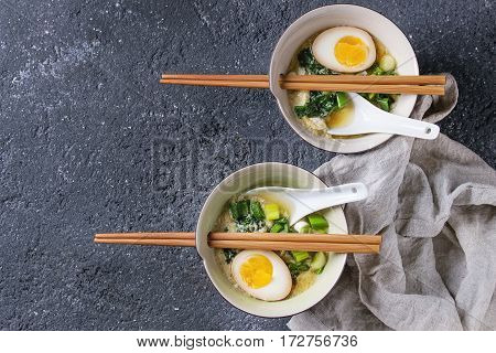 Two bowls with asian style soup with scrambled eggs, half of marinated egg, spring onion, spinach served with wood chopsticks and spoons over black texture concrete background. Top view with space