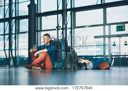 Two friends traveling together. Travelers waiting at the airport departure area for their a flight.