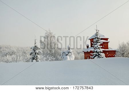 Snow Covered Orthodox Chapel Amidst Winter Fir Trees In Deep Snow