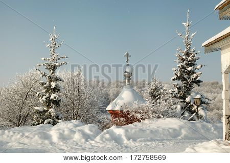 Cross On The Winter Covered Dome Amidst Snowy Fir Trees