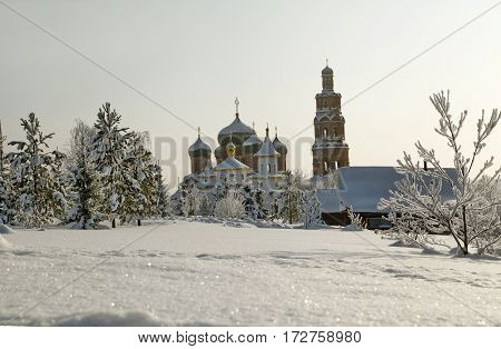 Orthodox Monastery With Snow Covered Domes In Snowy Area With Bare Trees