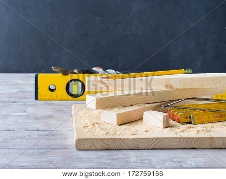 Wooden board with tools for manual measuring cutting - meter, level, pencil. Bricolage hand made DIY design craft project. Black background